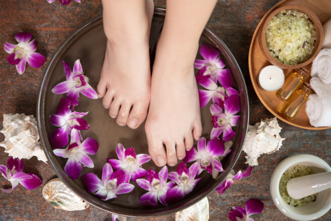 spa-treatment-product-female-feet-hand-spa-orchid-flowers-ceramic-bowl